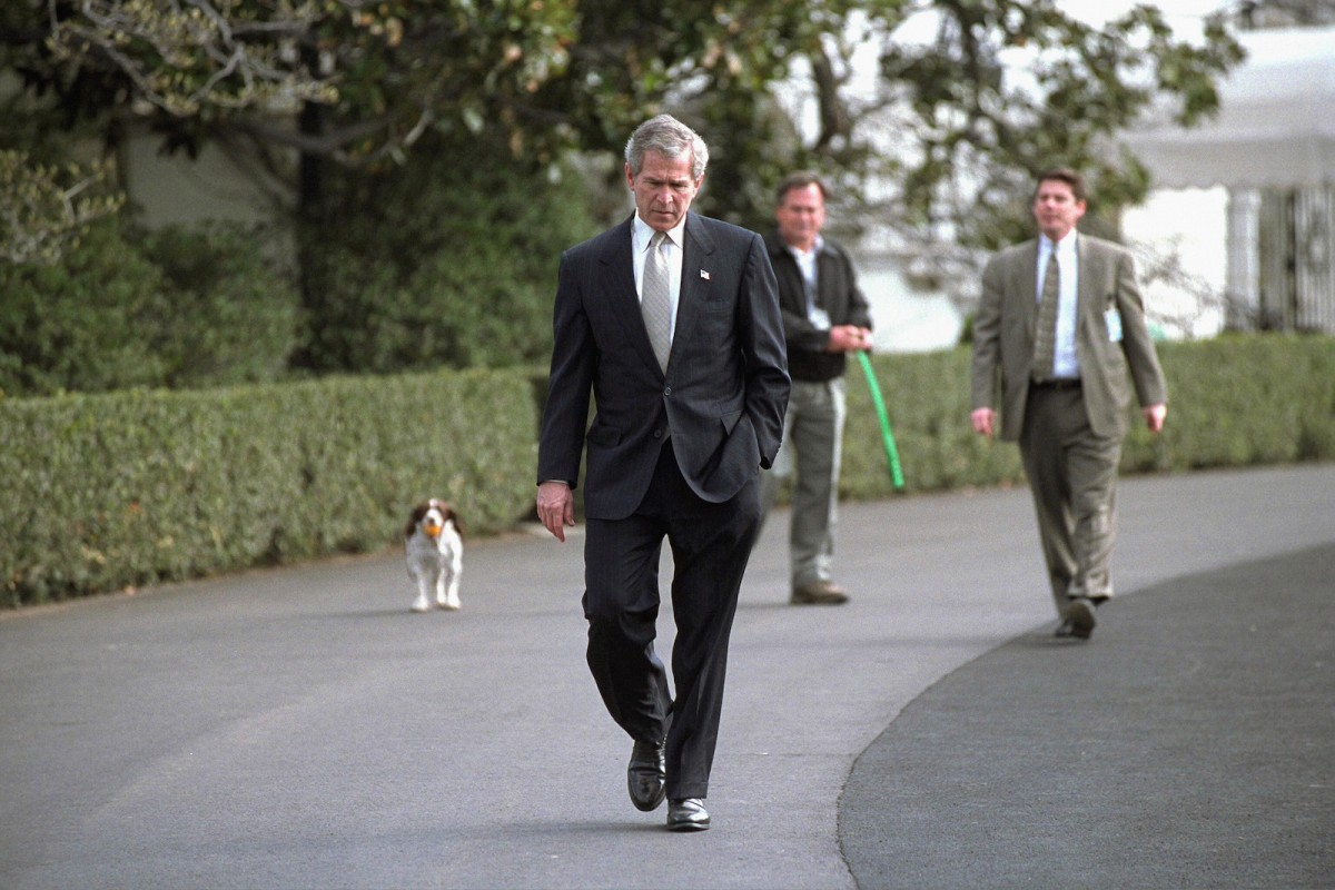 Followed closely by his dog Spot, President George W. Bush walks on the South Lawn Wednesday, March 19, 2003. In an address to the nation that evening, President Bush announced the start of Operation Iraqi Freedom.