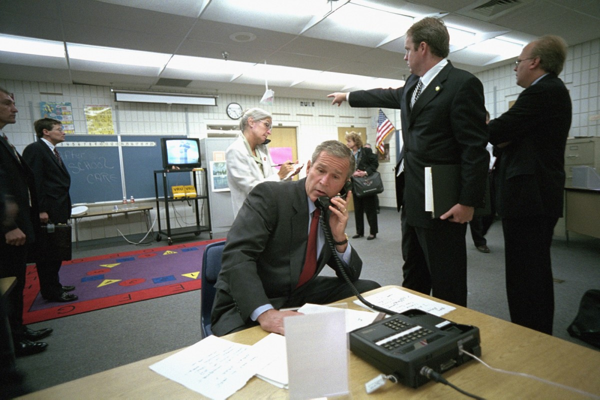 As Deputy Assistant Dan Bartlett points to news footage of the World Trade Center, President George W. Bush gathers information about the attack Tuesday, Sept. 11, 2001, from a classroom at Emma E. Booker Elementary School in Sarasota, Fla. Also pictured are Director of White House Situation Room Deborah Loewer, directly behind the President, and Senior Advisor Karl Rove, far right.  Photo by Eric Draper, Courtesy of the George W. Bush Presidential Library